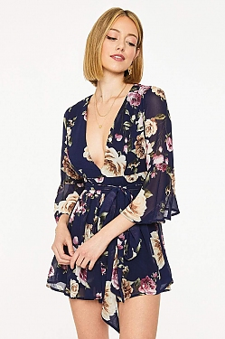 See Navy Flirty Floral Plunging Neck Romper in Navy